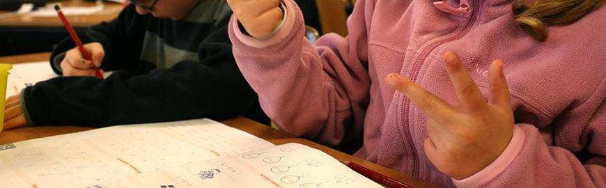 Elève qui compte sur ses doigts devant un manuel de mathématiques.  PROF/FWB/Michel Vanden Eeckhoudt