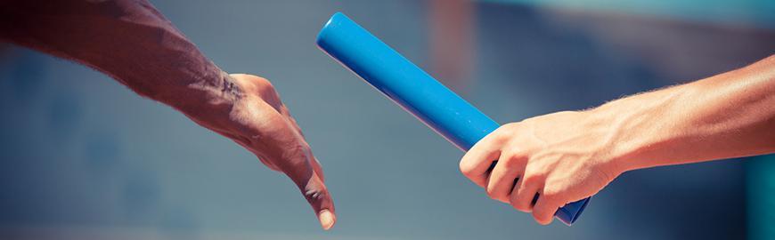 Un baton de relai passe d'une main à une autre.  Fotolia/William87