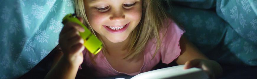 Jeune fille qui lit un livre dans le noir  Fotolia / Wordley Calvo Stock