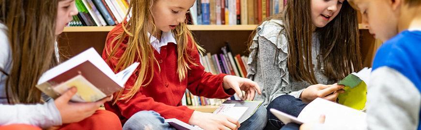 Des enfants lisent un livre en classe.